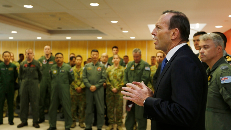 Australian Prime Minister Tony Abbott addresses the international forces currently based in Perth searching for Malaysia Airlines flight MH370 during his visit to RAAF Base Pearce near Perth, Monday, March 31, 2014. (AP / Jason Reed)