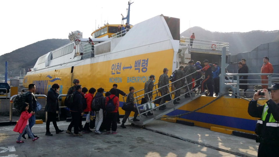 South Korean soldiers and islands' residents reembark a vessel bound for Baengnyeong island, as they evacuate from Daecheong island near the West Sea border with North Korea, Monday, March 31, 2014. (Ongjin County)