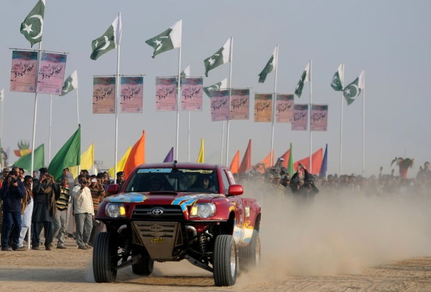 A Pakistani jeep driver drives past spectators