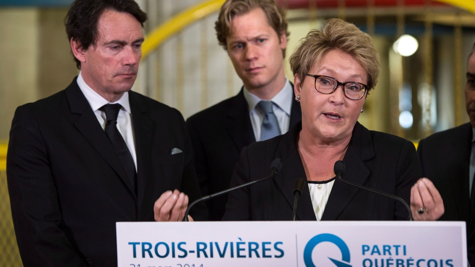 Parti Quebecois Leader Pauline Marois speaks while flanked by candidates Pierre Karl Peladeau, left, and Alexis Deschenes during a news conference in Trois-Rivieres, Que., Monday, March 31, 2014. (Paul Chiasson / THE CANADIAN PRESS)