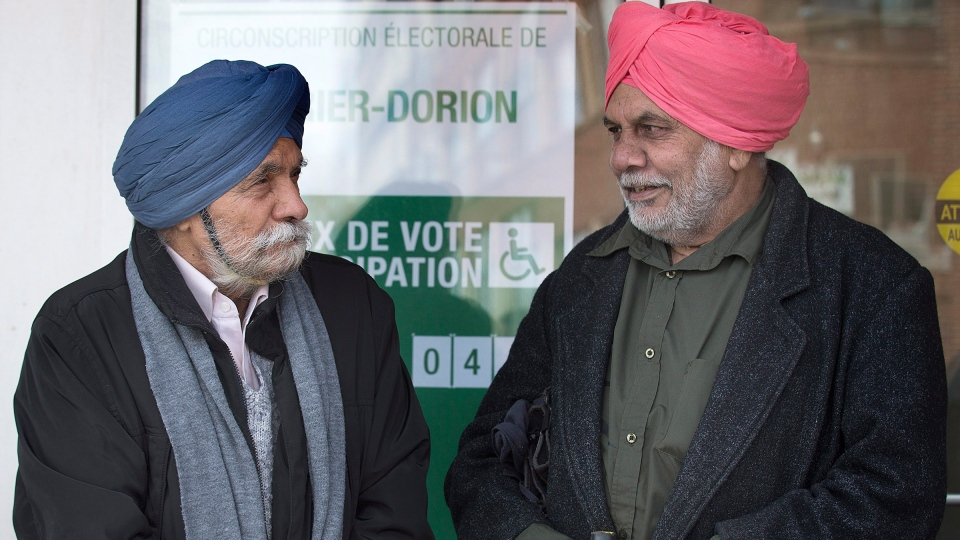 Two Sikh men chat outside an advance polling station in Montreal, Monday, March 31, 2014. (Graham Hughes / THE CANADIAN PRESS)