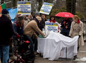 Protesters sign a mannequin on a gurney in Victoria Park, as they rally to support public health funding, in Halifax on Monday, March 31, 2014. Advocates fear Canadians may face bed shortages and more expensive drugs now that the 10-year, $41-billion health-care deal between Ottawa and the provinces has expired. The mannequin, covered with signatures from protesting citizens, will be presented to Nova Scotia Premier Stephen McNeil. (THE CANADIAN PRESS/Andrew Vaughan)
