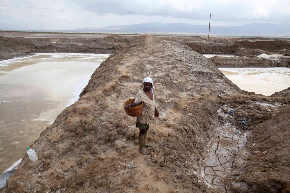 A worker, suffering from heat exhaustion, leaves her shift early at the salt evaporation ponds in Anse-Rouge, northwestern Haiti as drought hits the region, one of the hungriest, most desolate parts of the most impoverished nation in the hemisphere on Wednesday, March 26, 2014. (AP / Dieu Nalio Chery)