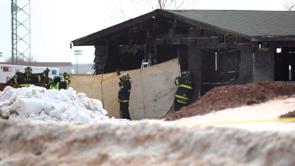 Charlottetown firefighters hold a tarp as officials remove bodies from an early morning fire in Charlottetown, P.E.I., Saturday, March 29, 2014. (Nathan Rochford / THE CANADIAN PRESS)