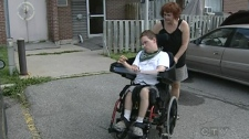 Jolanta Stansinska helps her son Jakub, 18, in his wheelchair (Oct. 13, 2011)