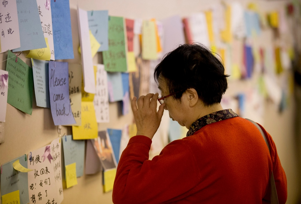 A woman, one of the relatives of Chinese passengers aboard the missing Malaysia Airlines flight MH370, looks at messages of wish for the passengers, at a hotel in Beijing, Tuesday, April 1, 2014. (AP / Andy Wong)