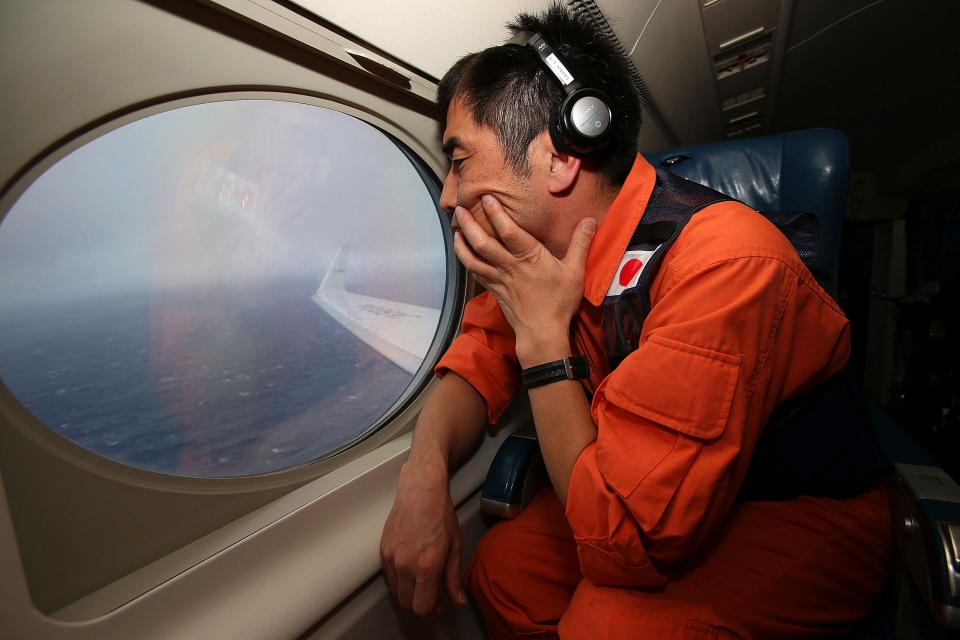 Koji Kubota of the Japan Coast Guard keeps watch through a window of their Gulfstream V aircraft while flying in the search zone for debris from the missing Malaysia Airlines flight MH370 off Perth, Australia, Tuesday, April 1, 2014. (AP / Paul Kane)
