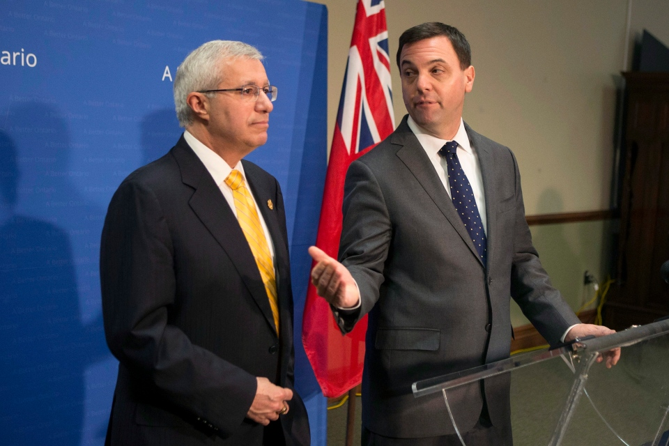 Ontario PC Leader Tim Hudak, right, stands with PC finance critic Nick Fedeli as they scrum with media ahead of question period at the Queen's Park in Toronto, Tuesday, April 1, 2014. (Chris Young / THE CANADIAN PRESS)