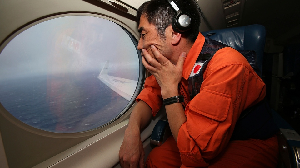 Koji Kubota of the Japan Coast Guard keeps watch through a window of their Gulfstream V aircraft while flying in the search zone for debris from the missing Malaysia Airlines flight MH370, off Perth, Australia, Tuesday, April 1, 2014. (AP / Paul Kane)