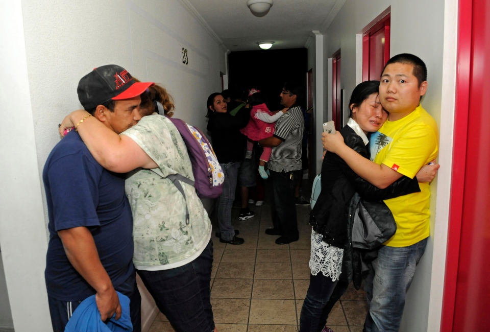People embrace on the upper floor of an apartment building located a few blocks from the coast where they gathered to avoid a possible tsunami after an earthquake in Iquique, Chile, Tuesday, April 1, 2014. (AP / Cristian Viveros)