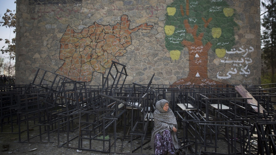 An Afghan woman sits on destroyed school benches as she waits to get her registration card on the last day of voter registration for the upcoming presidential elections outside a school in Kabul, Afghanistan, Tuesday, April 1, 2014. Elections will take place on April 5, 2014. (AP / Anja Niedringhaus)