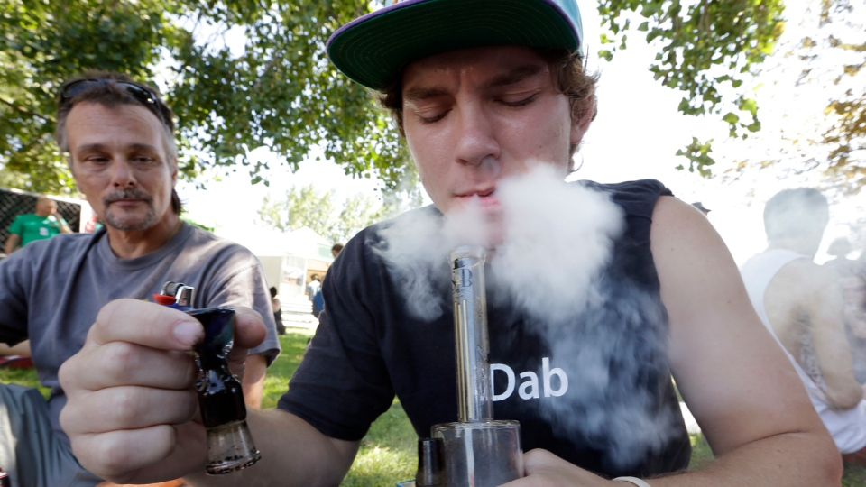 Cody Park exhales a cloud of marijuana smoke after taking a hit from a bong at the first day of Hempfest in Seattle, Friday, Aug. 16, 2013. (AP / Elaine Thompson)