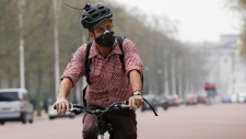 A cyclist wears an anti air pollution mask as he cycles along The Mall in London, Wednesday, April 2, 2014.  (AP Photo/Kirsty Wigglesworth)