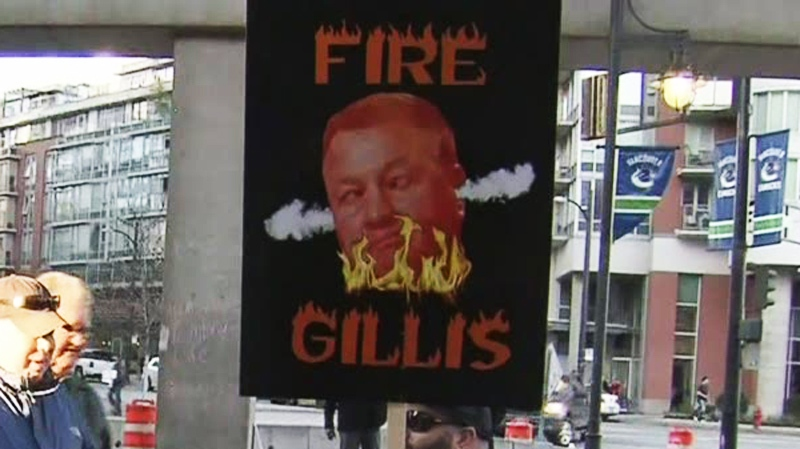 "Fans carry ""Fire Gillis"" signs outside Rogers Arena protesting Canucks management decisions. April 2, 2014. (CTV)"