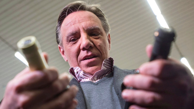 Coalition Avenir Quebec leader Francois Legault checks out bottles of wine from a local producer Tuesday, April 1, 2014 in St-Hyacinthe, Que. THE CANADIAN PRESS/Paul Chiasson