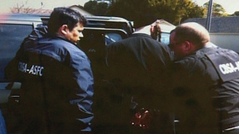 A member of Lev Tahor is seen being arrested in Chatham, Ont., on Wednesday, April 2, 2014.