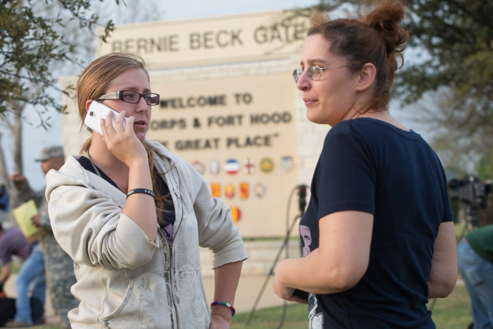 Krystina Cassidy and Dianna Simpson attempt to make contact with their husbands who are stationed inside Fort Hood, while standing outside of the Bernie Beck Gate in Fort Hood, Texas, Wednesday, April 2, 2014. (AP / Tamir Kalifa)