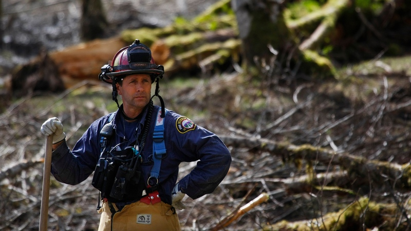Capt. Jeff Zonrnes, of the Monroe Fire Department, looks on in the debris field, Wednesday, April 2, 2014, as volunteers worked to clear more of the mudslide area in Oso, Wash. A deadly mudslide in March killed more than two dozen people. (AP / The Herald, Genna Martin)