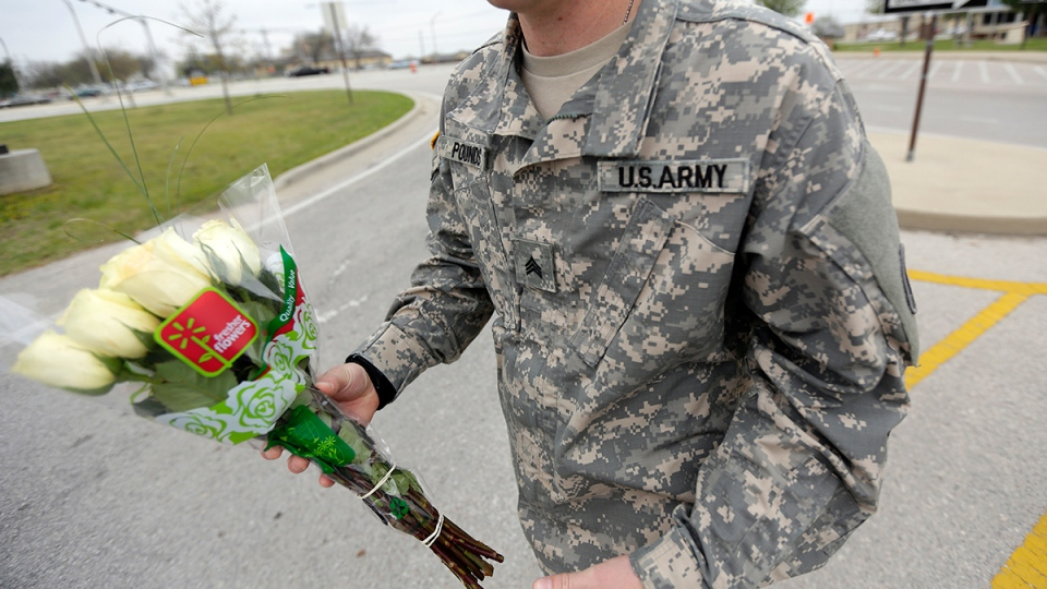 An unidentified soldier holds flowers dropped off at Fort Hood's main gate for shooting victims, in Fort Hood, Texas, Thursday, April 3, 2014. (AP / Eric Gay)