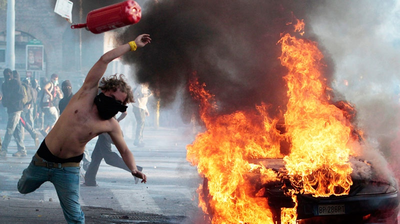 A protester hurls a canister clashes in Rome, Saturday, Oct. 15, 2011.