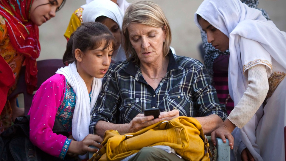 Canadian reporter and AP Special Regional Correspondent Kathy Gannon sits with girls at a school in Kandahar, Afghanistan, Oct 1, 2011. (AP / Anja Niedringhaus)