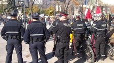 About twenty police officers have assembled at Churchill Square as the crowd of people in the downtown core continues to grow on Saturday, October 15.