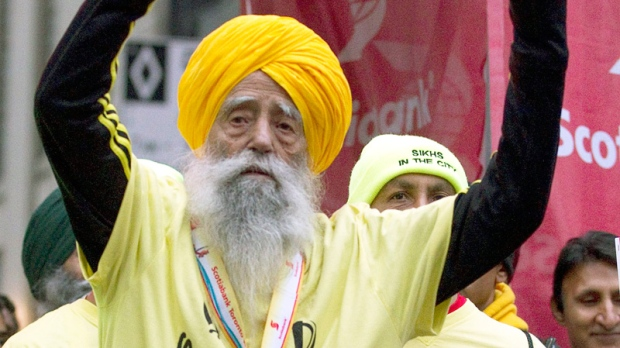 Fauja Singh, aged 100, celebrates after crossing the line in the Toronto Waterfront Marathon in Toronto on Sunday, Oct. 16, 2011. (Frank Gunn / THE CANADIAN PRESS)
