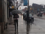A pedestrian hides under an umbrella on a rainy day in Toronto Friday, April 4, 2014. (Chris Kitching/CP24)
