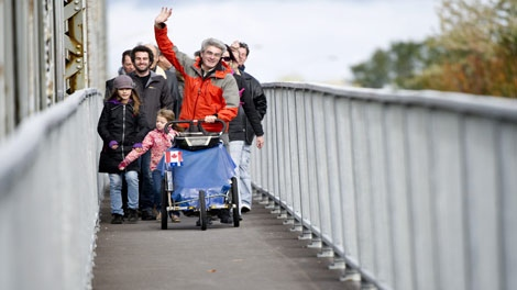 Jean Beliveau crosses a bridge as he arrives in Montreal following an 11-year walking trek around the world to promote peace Sunday, October 16, 2011 in Montreal. THE CANADIAN PRESS/Paul Chiasson