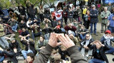 Protesters practise communication hand signals in a staging area at a downtown church grounds in Toronto, Sunday, Oct. 16, 2011. (J.P. Moczulski / THE CANADIAN PRESS)