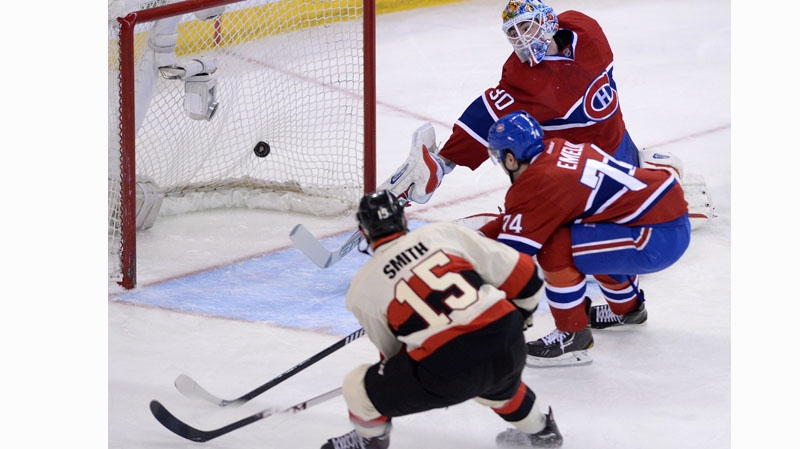 Ottawa Senators forward Zack Smith (15) blasts the puck past Montreal Canadiens goalie Peter Budaj and defenceman Alexei Emelin during first period NHL hockey action in Ottawa on Friday, April 3, 2014. THE CANADIAN PRESS/Sean Kilpatrick