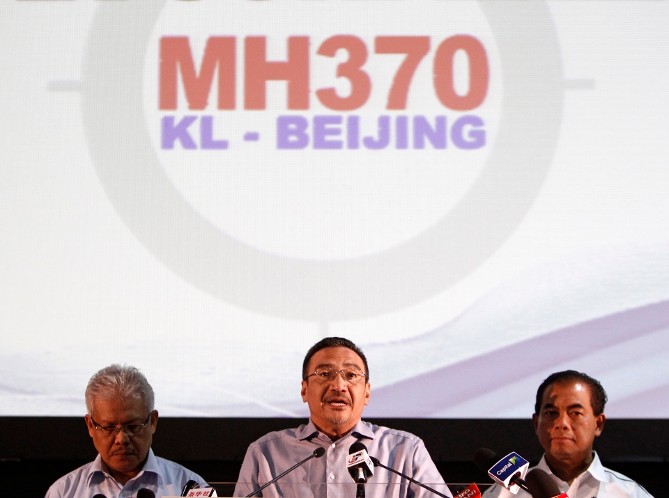 Malaysian acting Transport Minister Hishammuddin Hussein, center, speaks as Malaysian Deputy Foreign Minister Hamzah Zainuddin, left, and Malaysian Deputy Transport Minister Abdul Aziz Kaprawi listen during a press conference for the missing Malaysia Airlines Flight MH370, in Kuala Lumpur, Malaysia, Saturday, April 5, 2014. (AP / Lai Seng Sin)