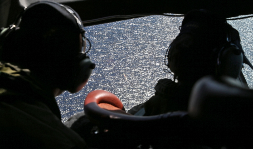 Wing commander Rob Shearer captain of the Royal New Zealand Air Force P3 Orion left, and Sgt. Sean Donaldson look out the cockpit windows during search operations for missing Malaysia Airlines Flight MH370 in the southern Indian Ocean, near the coast of Western Australia, Friday, April 4, 2014.(AP / Nick Perry/Pool)
