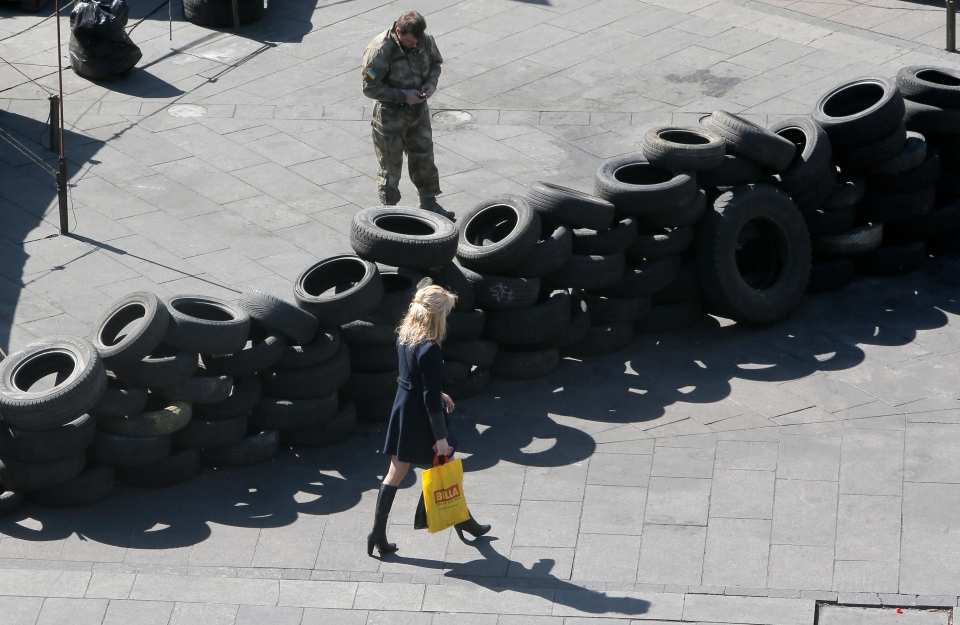 A passerby goes along a tire barricade in Kyiv's Independent Square on Saturday, April 5, 2014. (AP Photo/Efrem Lukatsky)