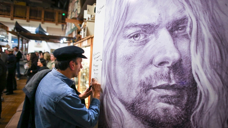 Warren Mason, Kurt Cobain's first guitar teacher, signs an image of the musician during the first annual Kurt Cobain Day on Thursday, Feb. 20, 2014 in Aberdeen, Wash. (AP Photo/seattlepi.com, Joshua Trujillo)