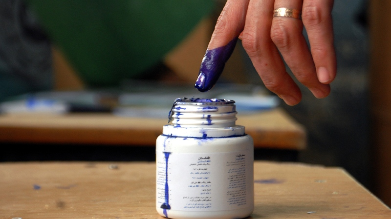 An Afghan woman puts her finger into an ink bottle to mark herself as a voter who attended an election at a polling station in Mazar-i-Sharif, capital of Balkh province, Afghanistan, Saturday, April 5, 2014. (AP / Mustafa Najafizada)