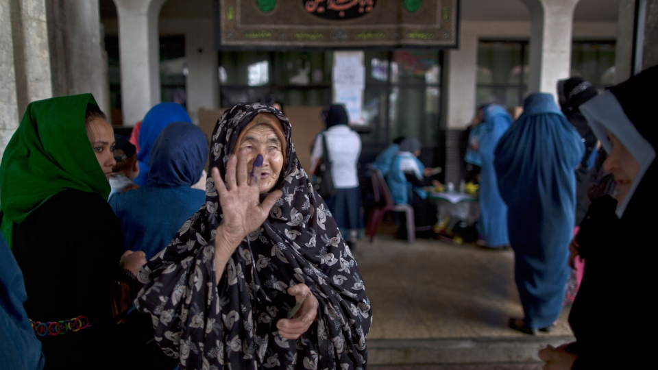 An elderly Afghan woman shows another woman her inked finger after casting her ballot at a polling station in Kabul, Afghanistan, Saturday, April 5, 2014. (AP / Muhammed Muheisen)