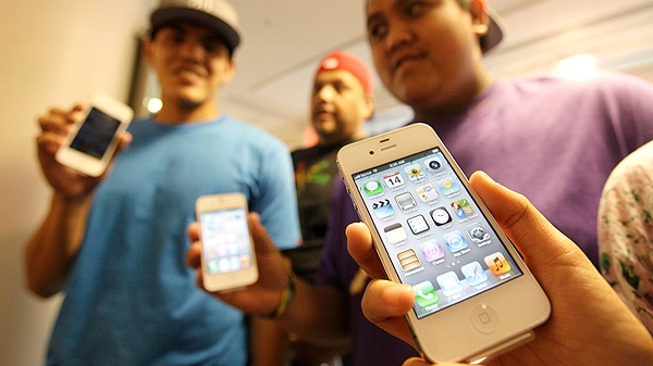 The Leon Guerrero family, on vacation from Dallas, show off their new Apple iPhone 4S phones they purchased at a Sprint store in San Francisco, Friday, Oct. 14, 2011. (AP Photo/Eric Risberg)