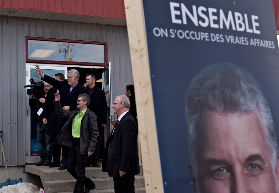 Quebec Liberal Party Leader Philippe Couillard waves to supporters as he walks out his home riding headquarter following a campaign blitz across the province, in Roberval Que., on Sunday, April 6, 2014. (Jacques Boissinot / THE CANADIAN PRESS)