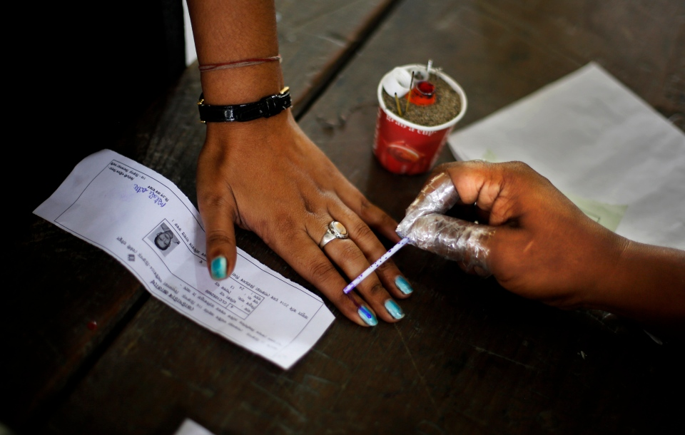 An Indian election officer applies an indelible ink mark on the finger of a woman during the first phase of elections in Dibrugarh, in the northeastern state of Assam, India, Monday, April 7, 2014. India started the world's largest election Monday. (AP/Altaf Qadri)