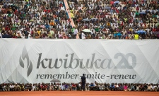 Crowds of Rwandans gather in front of a banner