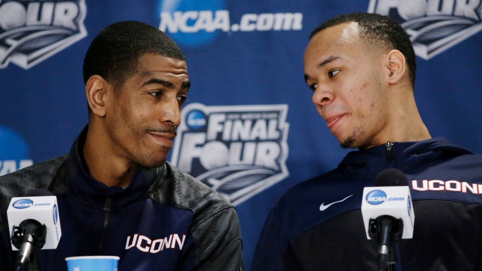 Connecticut head coach Kevin Ollie, left, and guard Shabazz Napier chat with each other during a news conference for the NCAA Final Four tournament college basketball championship game Sunday, April 6, 2014, in Arlington, Texas. Connecticut plays Kentucky in the championship game on Monday, April 7. 2014. (AP / David J. Phillip)