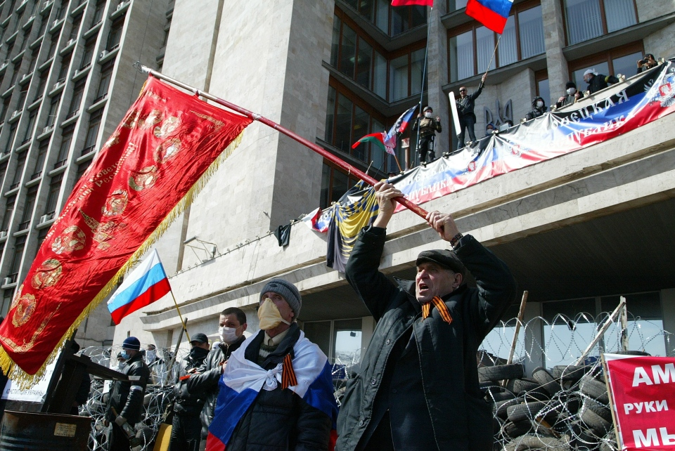 Activists wave an old Soviet and Russian national flags in front of a barricade at the regional administration building, in Donetsk, Ukraine, Monday, April 7, 2014. (AP / Alexander Ermochenko)