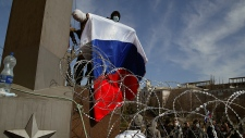 Pro-Russian activist wave flag at Donetsk building