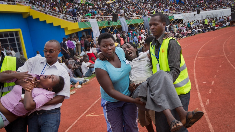 Two wailing and distraught Rwandan women, some of dozens overcome by grief at recalling the horror of the genocide, are carried away to receive help during a public ceremony to mark the 20th anniversary of the Rwandan genocide, at Amahoro stadium in Kigali, Rwanda, Monday, April 7, 2014. (AP / Ben Curtis)