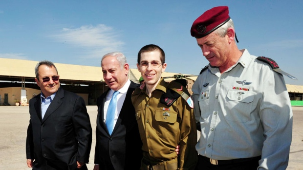 In this photo released by the Israeli Defense Ministry, released Israeli soldier Gilad Schalit, second right, walks with Israeli Prime Minister Benjamin Netanyahu, second left, Defense Minister Ehud Barak, left, and Israeli Chief of Staff Lt. Gen. Benny Gantz, right, at the Tel Nof Air base in southern Israel, Tuesday, Oct. 18, 2011. (AP / Defense Ministry)