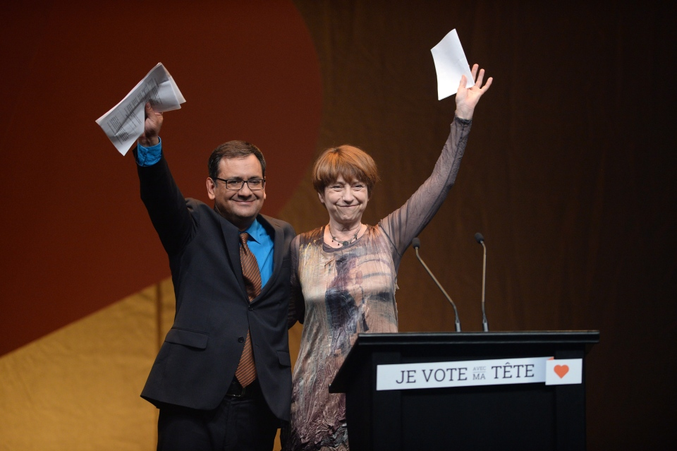 Quebec Solidaire co-leaders Andres Fontecilla, left, and Francoise David wave following their speeches in Montreal, Quebec on Monday, April 7, 2014. (Sean Kilpatrick / THE CANADIAN PRESS)