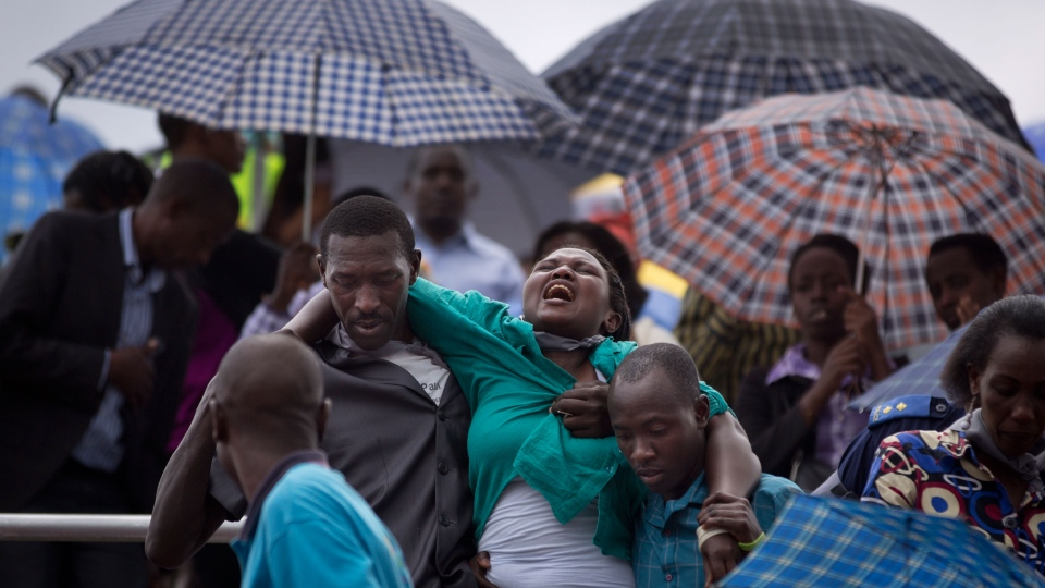 A wailing and distraught Rwandan woman, one of dozens overcome by grief at recalling the horror of the genocide, is carried away to receive help during a public ceremony to mark the 20th anniversary of the Rwandan genocide, at Amahoro stadium in Kigali, Rwanda, Monday, April 7, 2014. (AP / Ben Curtis)