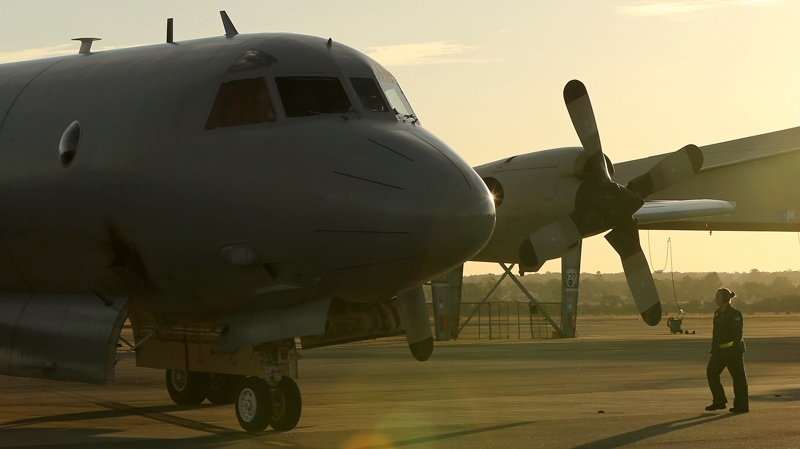 A flight crewman from a Royal Australian Air Force P-3 Orion walks towards the aircraft at RAAF Base Pearce as it arrives back from the on-going search operations for missing Malaysia Airlines Flight MH370 in Perth, Australia, Tuesday, April 8, 2014. (AP Photo/Rob Griffith)