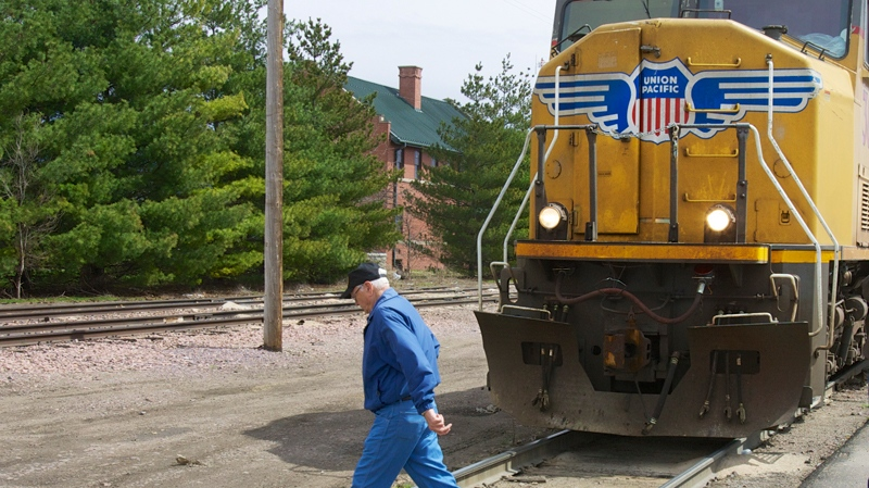 In this photo taken on April 7, 2010, a man crosses a railroad track in front of a stationary locomotive in Fremont, Neb. (AP Photo/Nati Harnik)